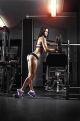 athletic young sexy girl sets weight on barbell in the gym