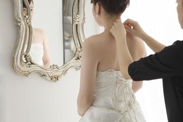 Bridesmaid is wearing a necklace to bride