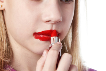 Girl paints her lips with red lipstick
