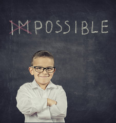 smart smiling boy standing in front of blackboard