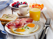 Breakfast with two fried eggs, toasts, orange juice and coffee. - 77920931