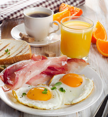 Breakfast with two fried eggs, bacon,toasts, juice and coffee.