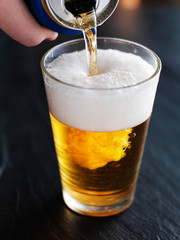 filling up a glass with beer from can