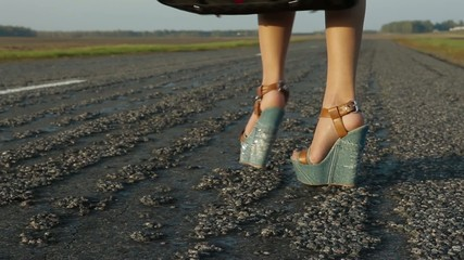 Women's feet are on the road hitch-hiking the car