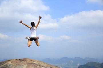 young asian woman jumping mountain peak cliff