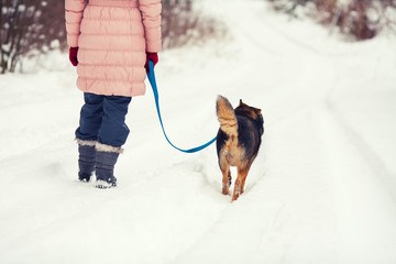 Young woman with dog walking on the snowy street back to camera