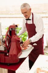 Italian man slicing ham