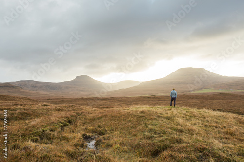 Man standing in Scottish Highland landscape
