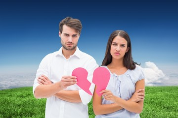 Upset couple holding two halves of broken heart