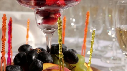 Delicious fruits on skewers in beautiful glass vase