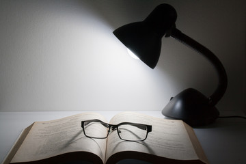 Reading glasses resting on top of open book next to night lamp