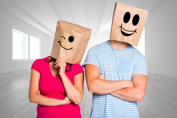 Composite image of young couple with bags over heads