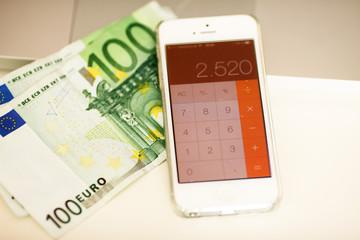 Geld und Taschenrechner am Smartphone