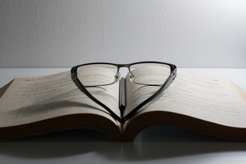 Open book and eyeglasses on desk