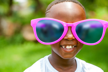 African boy wearing fun extra large sun glasses.