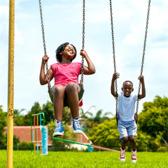 African kids having fun swinging in park.