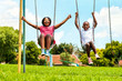 African kids playing on swing in neighborhood. - 77930157