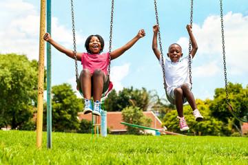 African kids playing on swing in neighborhood.