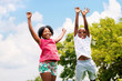 Two African kids jumping in park. - 77931375