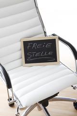 Symbolbild, Freie Stelle, weisser Bürostuhl mit Kreidetafel