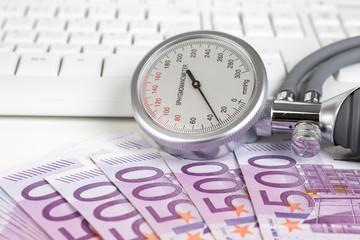 Blutdruckmessgerä liegt auf 500 Euroscheinen
