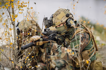 soldier with a rifle aiming at a target