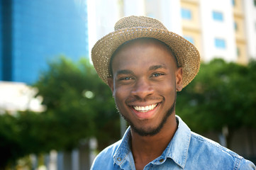 Young african american man smiling with hat