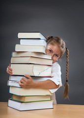 Little girl embraces a pile of books
