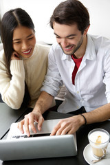 Cute happy couple working on laptop