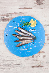 Fresh sardines on blue kitchen board.