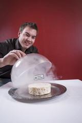 Mann vor einem Teller mit Käse und Käseglocke