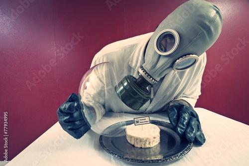 Leinwanddruck Bild Mann mit Gasmaske vor einem Teller mit Käse unter Käseglocke