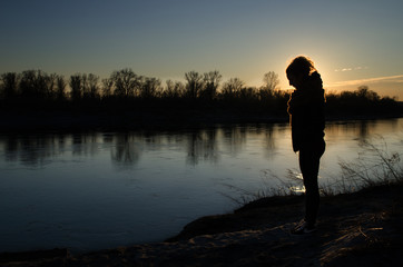 Young girl at sunset on the river bank