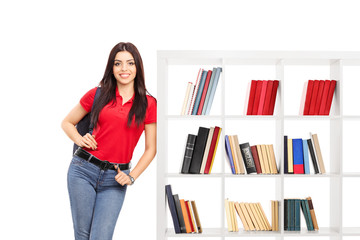 Female student leaning on a bookshelf