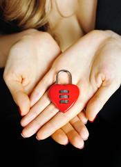 Padlock heart-shape in women's hands