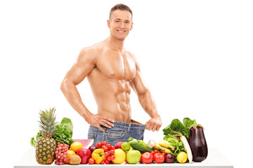 Handsome man posing behind a table with vegetables