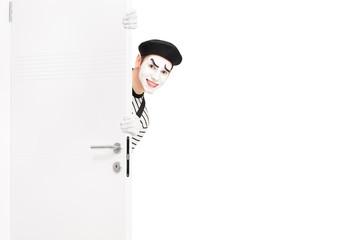 Smiling mime artist posing behind a wooden door