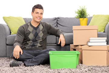 Man seated on the floor by a bunch of boxes