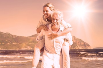 Man giving his laughing wife a piggy back at the beach