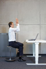 yoga on pneumatic seat at djustable desk with laptop