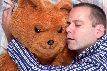 man sleeping in an embrace with a teddy bear