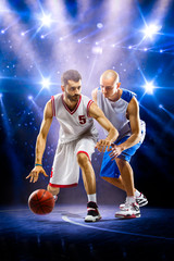 Two basketball players in spotlights