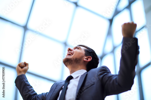 Leinwanddruck Bild businessman with arms up celebrating his victory