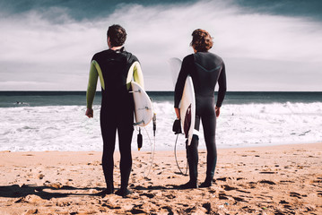 Two surfers are looking at the ocean and waiting a big  wave