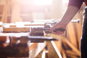 Carpenter gluing wooden planks
