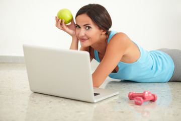 Pretty lady holding apple and working on computer