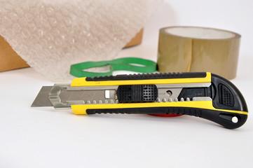 taglierino e nastro adesivo
