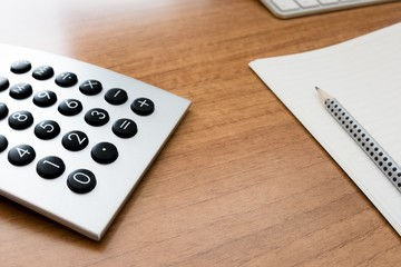 calculator on wooden desk with pencil and paper