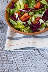 Appetizing tomato salad in bowl on wooden table