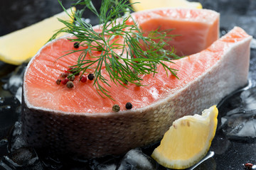 raw salmon steak with dill and lemon on ice, close-up